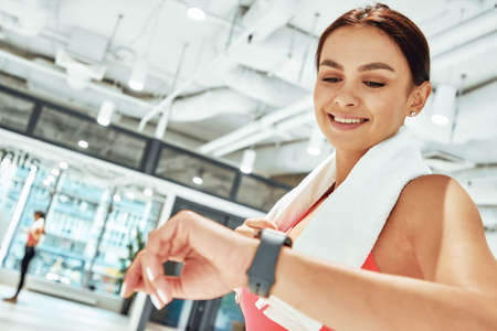 Young happy sportive woman with white towel on shoulders looking at smartwatch while exercising in fitness studio