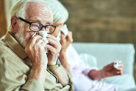 Male retiree using paper napkins for a cold