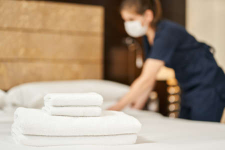 Housemaid preparing the room for the arrival of guests