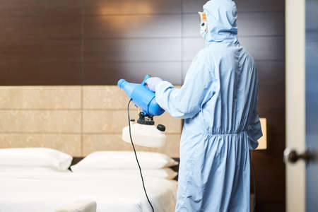 Worker holding the disinfectant and pointing it towards the middle of the room