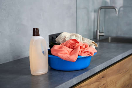 Time for laundry. Close up shot of liquid detergent and plastic basket with dirty laundry indoors Archivio Fotografico