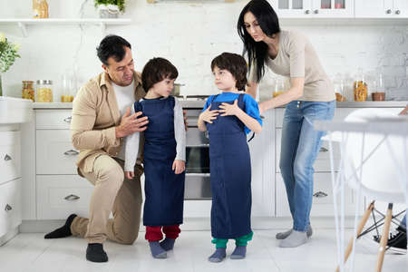 Assistants. Hispanic parents puttting on aprons on two little boys, twins while cooking dinner in the kitchen at home together