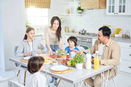 Share food. Caring hispanic woman serving salad for her husband and children, standing in the kitchen. Latin family having dinner together at home Foto de archivo