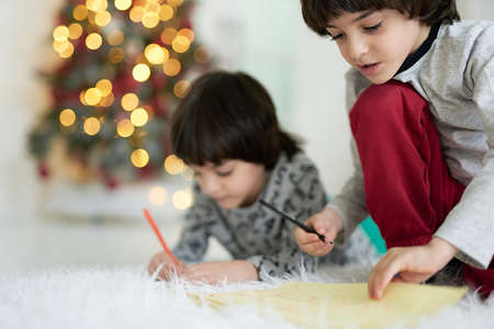 Close up shot of two little latin boys, twins drawing while sitting on the floor at home decorated for Christmas. Siblings involved in creative activity together