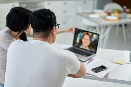 Learn new skills. Rear view of middle aged hispanic couple, man and woman communicating with tutor during online training course while studying remotely, using laptop at home 免版税图像