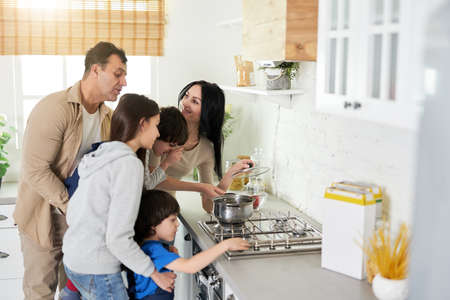 Cook together. Hispanic parents looking happy while standing in the kitchen with children and cooking dinner together at home