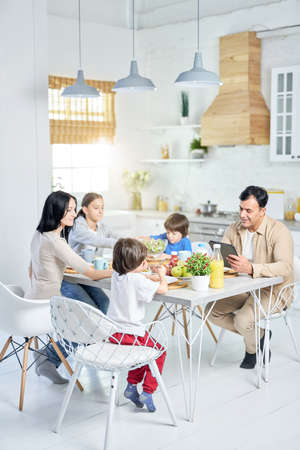Full length shot of cheerful hispanic family enjoying meal together while having lunch, sitting at the table in kitchen at home