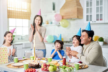 Special day. Joyful hispanic family with children looking happy, clapping while celebrating birthday together at home