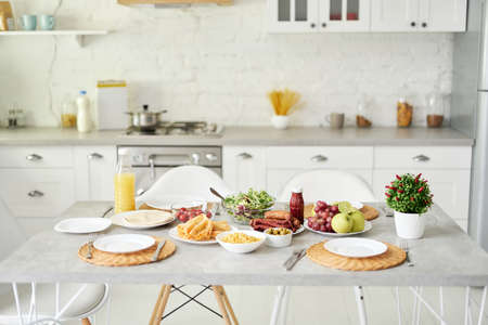 Bright kitchen. Latin style breakfast on the table. Modern bright white kitchen interior with wooden and white details