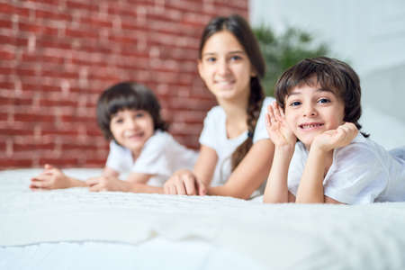 Portrait of cute little latin boy smiling at camera. Brother spending time with his siblings, lying on the bed at home Imagens