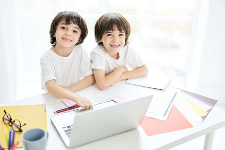 Best education for kids. Two adorable latin boys, brothers smiling at camera while sitting together at the table and using laptop. Little kids having online lesson at home