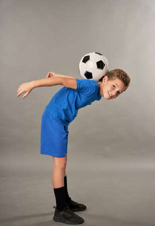 Cute boy with soccer ball on his back standing against gray background
