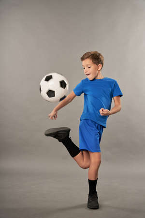 Little football player in sportswear kicking soccer ball 免版税图像