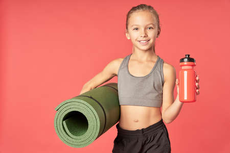 Cute sporty girl holding yoga mat and bottle of water
