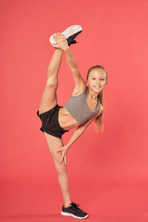 Adorable girl doing standing splits against red background