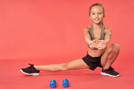 Cheerful female child doing exercise in studio