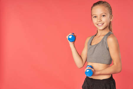 Adorable female child doing exercise with dumbbells