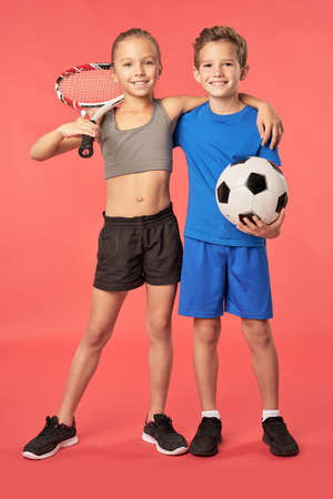 Adorable sporty kids standing against red background