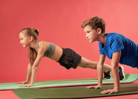 Adorable girl and boy doing plank against red background