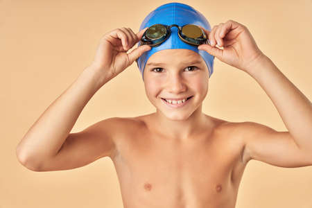 Joyful boy swimmer standing against light orange background