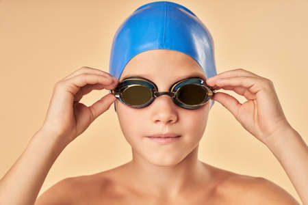Cute boy in swim goggles standing against light orange background 免版税图像