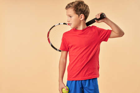 Cute boy tennis player standing against light orange background