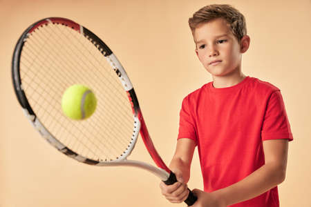 Adorable boy in red shirt playing tennis