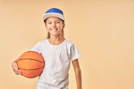 Joyful girl basketball player standing against light orange background