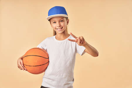 Adorable girl holding basketball ball and showing victory gesture