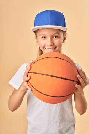 Adorable joyful girl in cap holding basketball ball 免版税图像