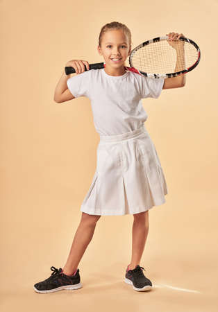 Cute girl tennis player standing against light orange background