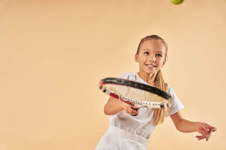 Cute female child playing tennis and smiling