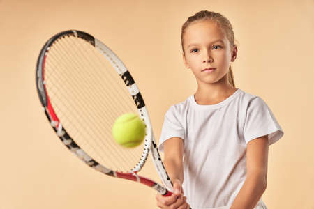 Adorable girl in white shirt playing tennis