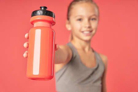 Cheerful sporty girl holding bottle of water