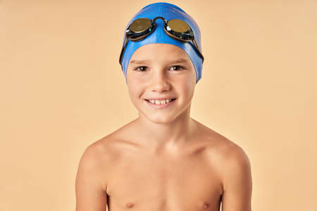 Cheerful boy swimmer standing against light orange background 免版税图像