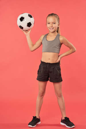 Cute female child with soccer ball standing against red background