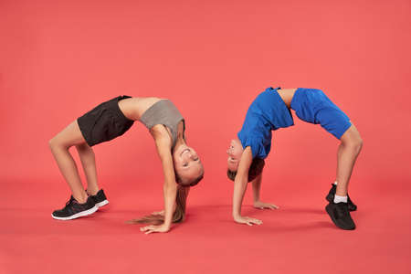 Adorable boy and girl doing gymnastic exercise in studio