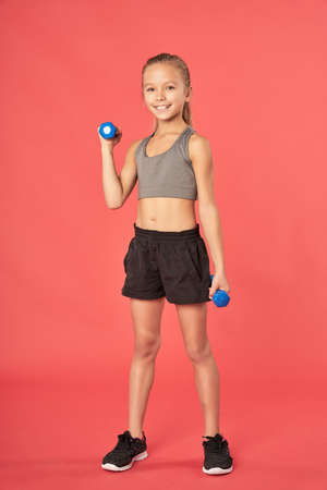 Cheerful sporty girl doing exercise with dumbbells