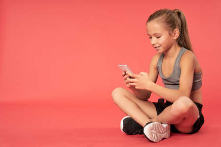 Adorable girl using cellphone against red background