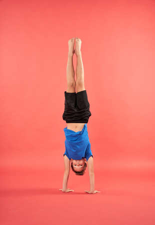 Adorable male child in sportswear doing handstand exercise