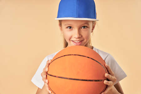 Adorable girl in sports cap holding basketball ball