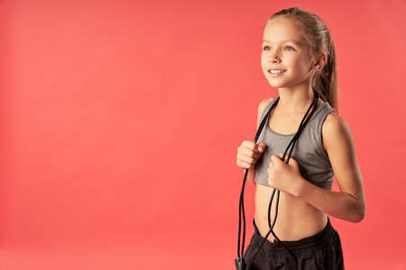 Adorable child with skipping rope standing against red background