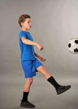 Little football player kicking the ball against gray background