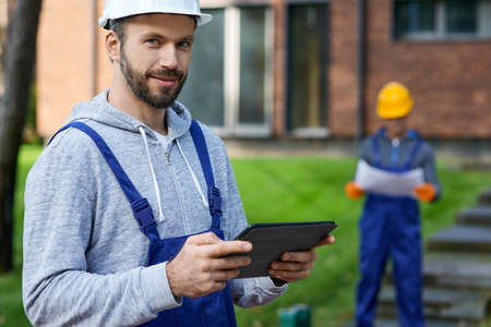 Portrait of young male builder smiling at camera while holding digital tablet pc with coworker working in the background at cottage construction site