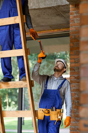 Young workman in overalls and hard hat giving hammer to his colleague on ladder while working at cottage construction site