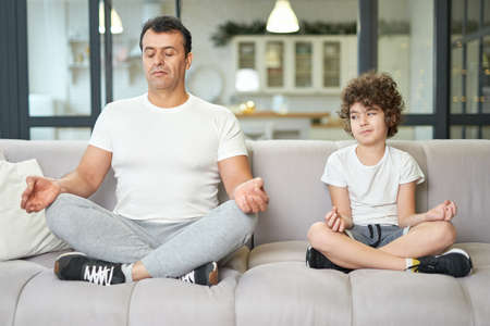 Calm down. Relaxed latin middle aged father teaching his son to meditate while they are sitting together on a couch at home