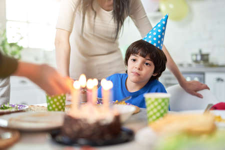 Cute little latin american boy in birtday cap looking at birthday cake while celebrating birthday with his family at home