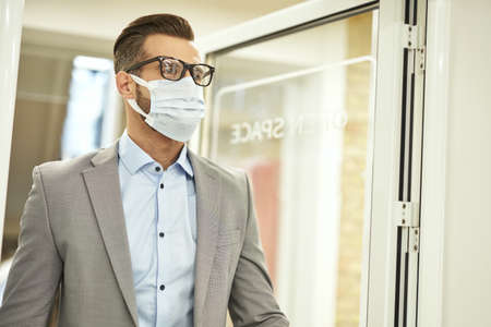 Elegant office manager wearing medical mask at work