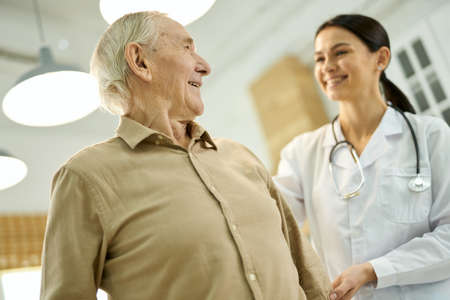 Cheerful aged man looking at his family doctor Foto de archivo