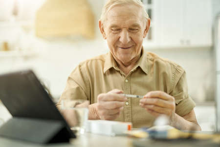 Cheered-up elderly man having a close look at syringe